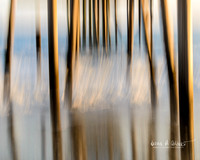 Reflections of pylons in wet sand under a pier